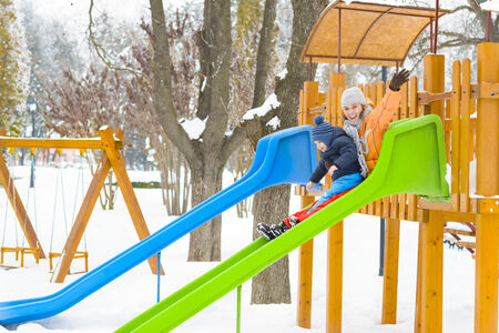 Mother and son playing on a slide in wintertime Stock Photo - 26280500