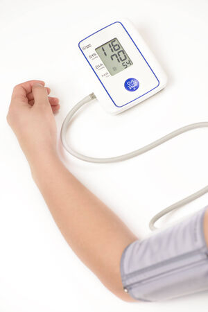 Woman measuring her own blood pressure Stock Photo