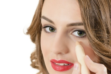 Beautiful young woman using concealer photo