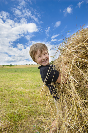 Kid playing with straw in a sunny summer day photo