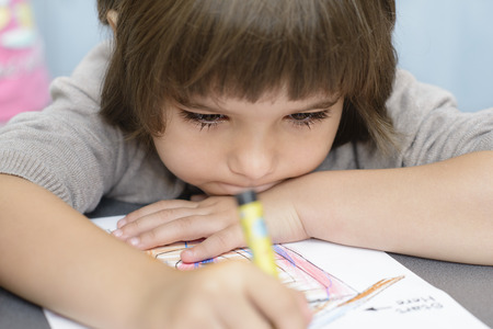 lonely girl: Lonely Girl drawing at kindergarten Stock Photo