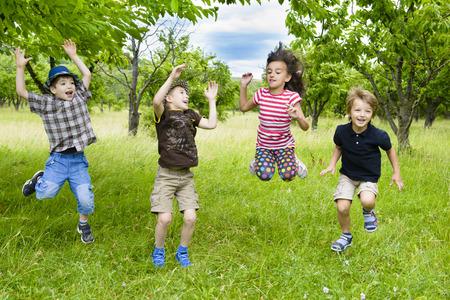 Kids Jumping in a orchard summer day Standard-Bild