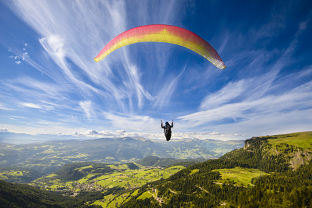 parachute jump: Paraglider flying over mountains in summer day Stock Photo