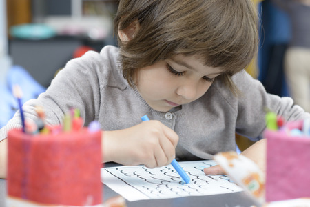 child drawing: Lonely Girl drawing at kindergarten Stock Photo