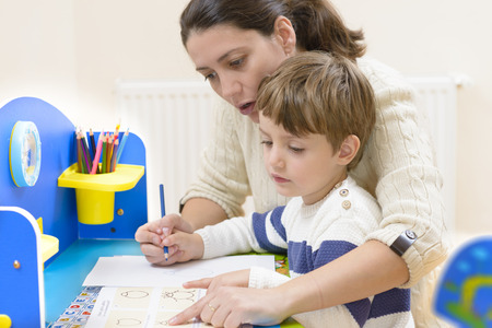 teaching crayons: Mother helping her kid to make drawings