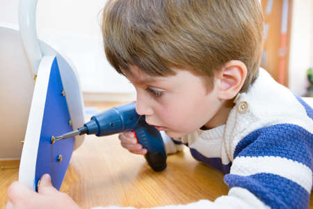 furniture hardware: Little Boy using diy tool at home Stock Photo