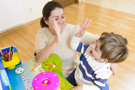 Mother playing with her child some creativity game and encouraging him