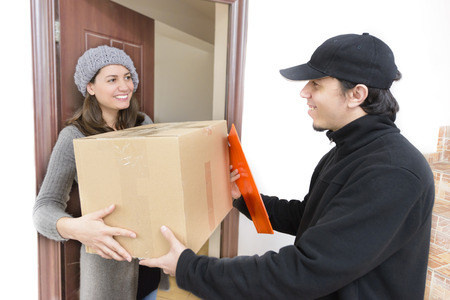 distribution box: Courier Delivering a Package to a happy woman Stock Photo