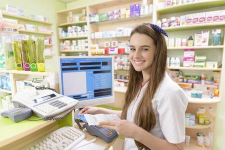 maquina registradora: Farmacéutico de sexo femenino joven que sostiene un recibo
