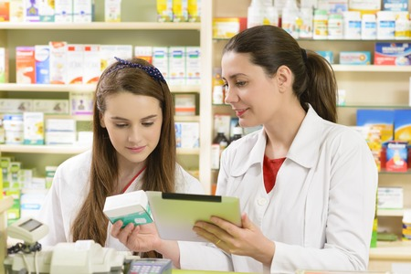 Two young female pharmacist in a drugstore working on a tablet pc