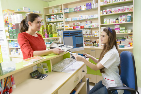 Young female pharmacist having a customer in a drugstore holding a receipt Banco de Imagens