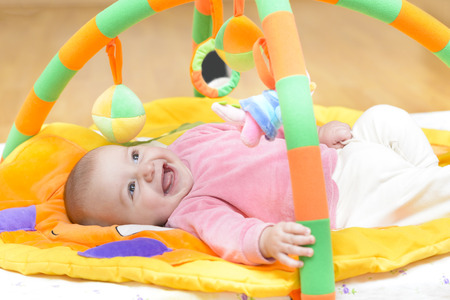 Innocent baby smiling and playing with toys Stock Photo