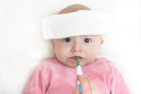 fiebre: Comprobaci�n de la temperatura a un beb� lindo con un term�metro digital