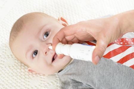 Woman using nasal spray for baby Standard-Bild