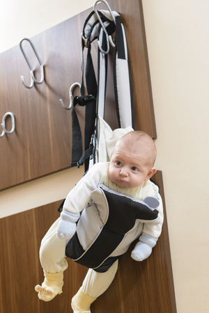 baby carrier: Cute baby sitting in a front baby carrier