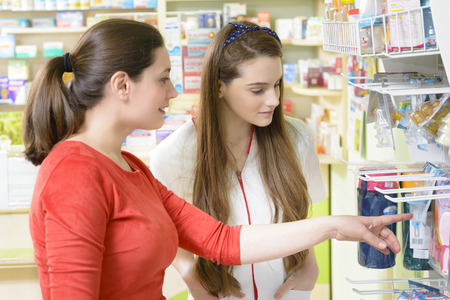 pharmaceutic: Young female pharmacist having a customer in a drugstore talking about babys feeding bottle Stock Photo