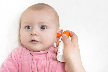 Auricular Hygiene. Woman using ear spray for baby.