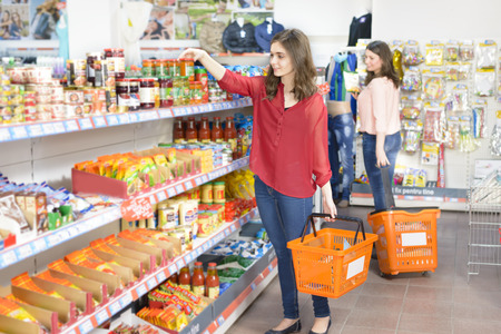 counters: Happy woman with shopping basket choosing products in supermarket