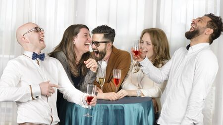 hilarious: Friends laughing hilarious in a bar, holding glasses of wine