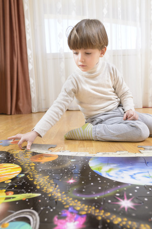 educational problem solving: Kid solving a floor puzzle at home