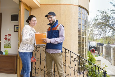 Courier Delivering a Package to a happy woman Banque d'images