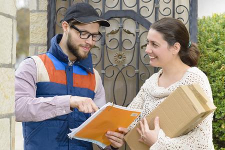 Corriere consegna un pacchetto di una donna felice Archivio Fotografico