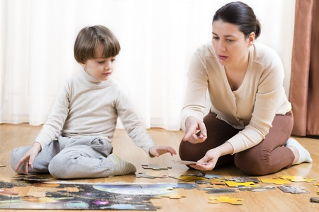 educational problem solving: Kid solving a floor puzzle at home being helped by his mother Stock Photo