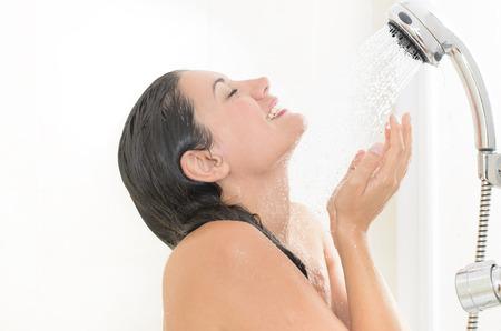 cabine de douche: Femme prenant une douche en appréciant les éclaboussures d'eau sur son