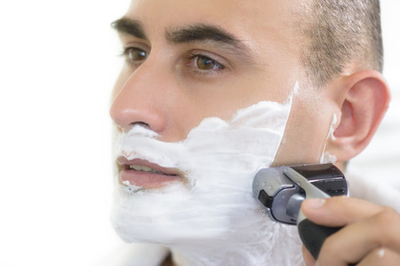 electric shaver: Young man shaving using electric shaver