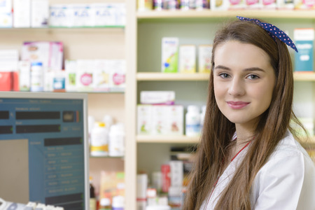 beauty products: Young female pharmacist at cash desk