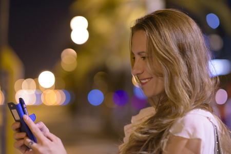 cellular: Beautiful blond woman using a smartphone, city lights in the background