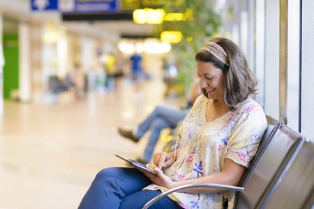 superficie: Mujer joven que usa una tableta digital en el área de espera del aeropuerto Foto de archivo