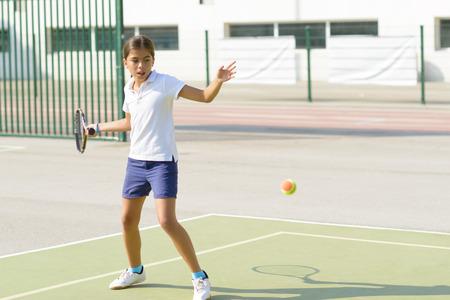 美しい少女のテニスコートでテニスをして