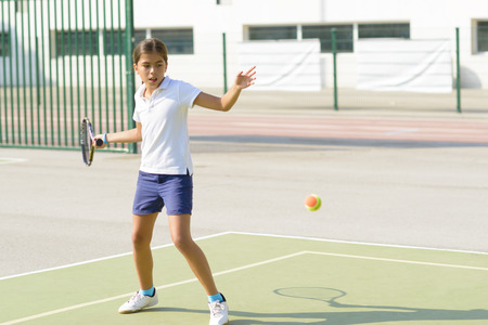 Beautiful girl playing tennis on tennis court