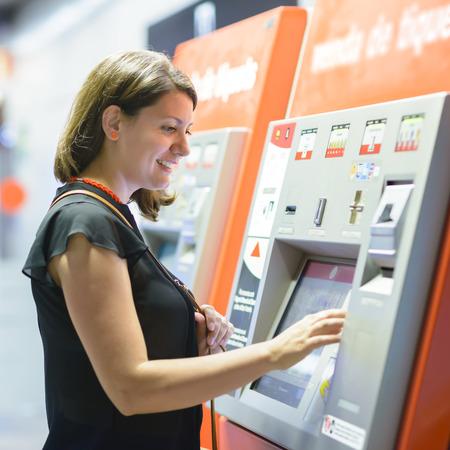 Mujer joven que paga en máquina expendedora de billetes en una estación de metro