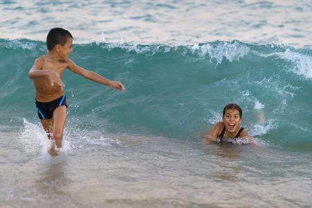 granola: Felices los niños jugando en el mar. Gran ola que viene en ellos