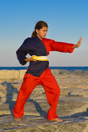 self defense: Beautiful girl practicing self defense on rocks near ocean Stock Photo