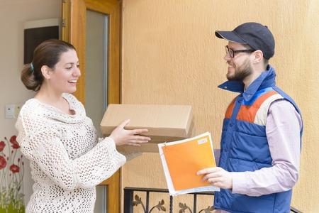 asombro: Mensajero que entrega un paquete a una mujer feliz