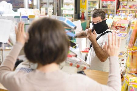 delincuencia: Ladrón enmascarado apuntando con un arma a la mujer de ventas en una tienda Foto de archivo