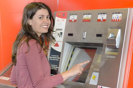 vending machine: Woman paying at an automatic machine