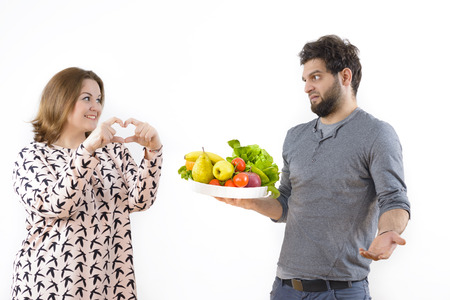 angry couple: Woman declaring love to her boyfriend but he constrain her to lose weight