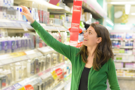 cosmetics: Happy woman choosing products in supermarket