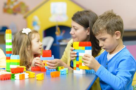 ni�os jugando en la escuela: Ni�os jugando con bloques de construcci�n de pl�stico en el jard�n de infantes