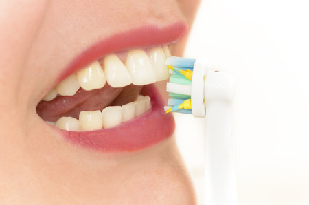 dental prophylaxis: Young woman using electric toothbrush looking in the mirror