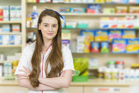 benevolence: Young female pharmacist at cash desk smiling with benevolence