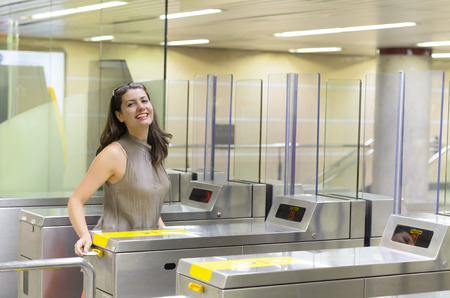 Beautiful woman entering at metro station, using the tickets