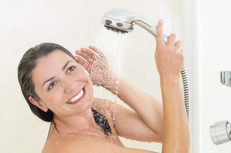 mujer bañandose: Mujer feliz que toma una ducha disfrutando de las salpicaduras de agua en su