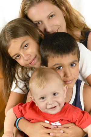 convivencia familiar: Familia feliz que disfrutan de unidad, sonriendo y abrazando aislados en blanco