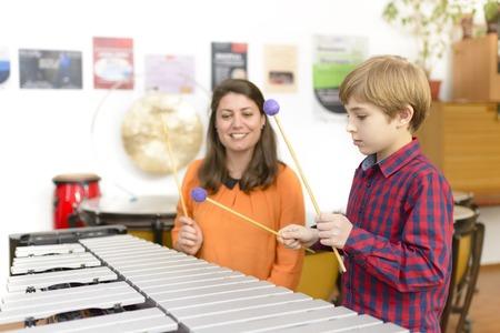 Kid studying percussion instrument vibraphone, teacher next to him