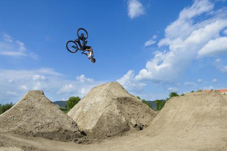 男は自転車の上で宙返り夏の日 写真素材